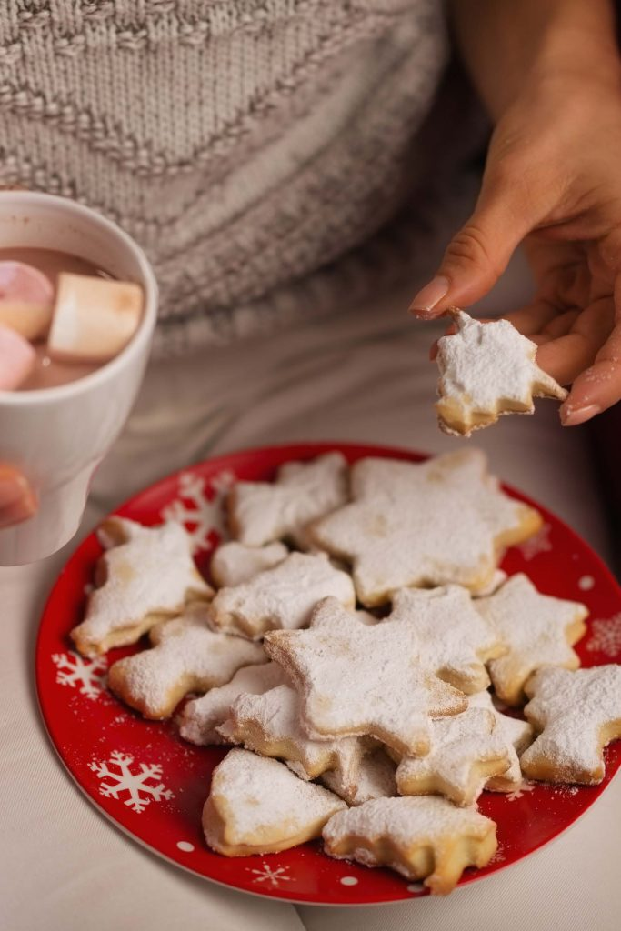 plate of holiday cookies on womans lap