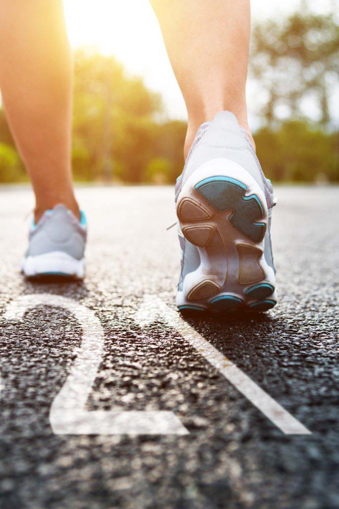 woman wearing sneakers walking over 2021 sign written on road
