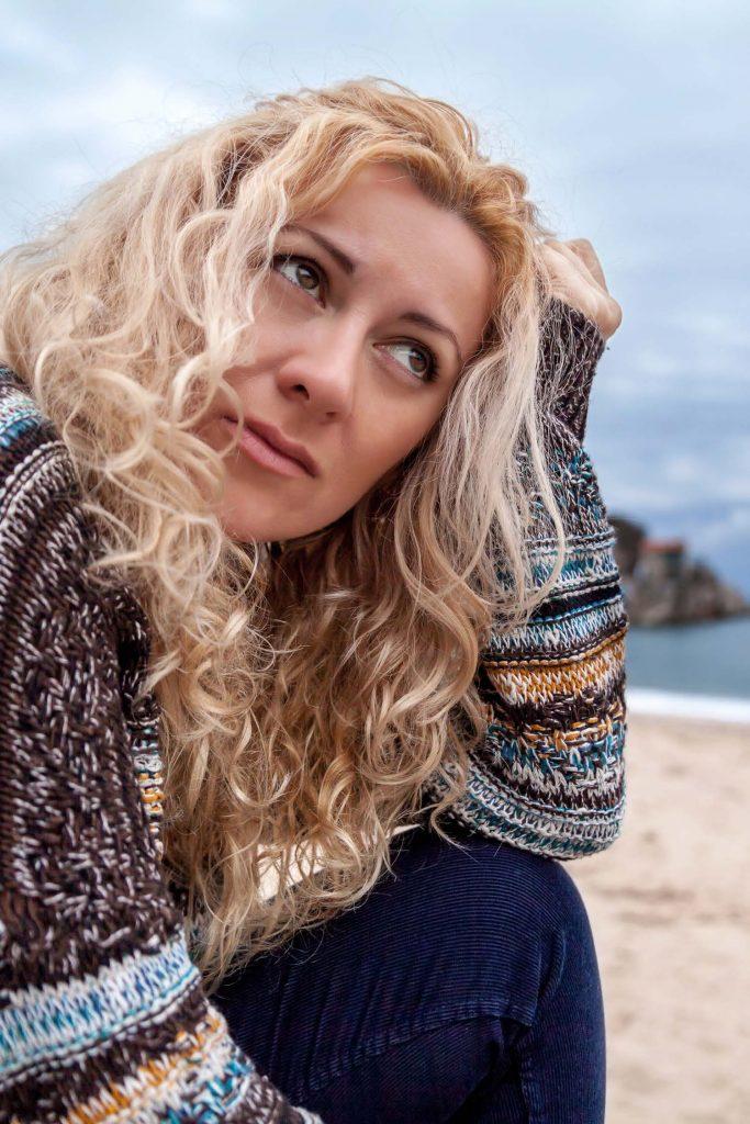 sad woman sitting on the beach thinking
