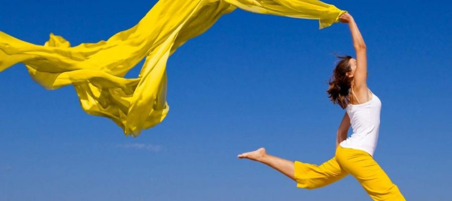 HodgeonRepeat blog - woman jumping on the beach holding yellow scarf
