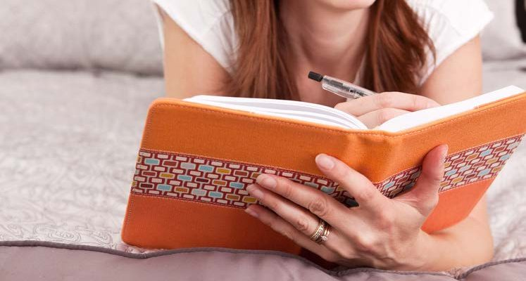 HodgeonRepeat blog - close up woman writing in orange journal - health and fitness journal prompts