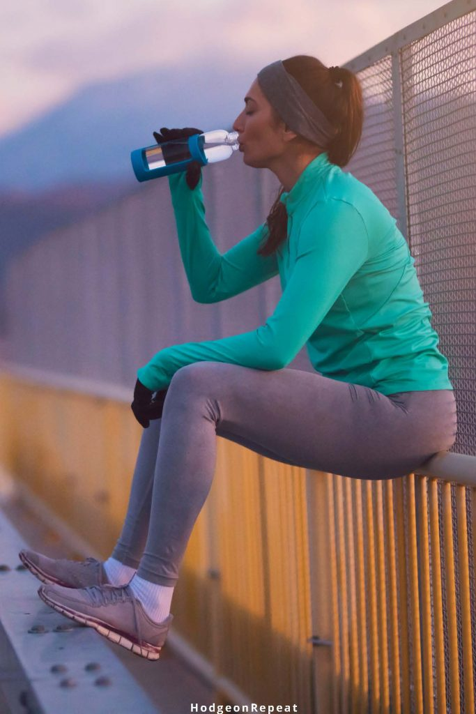 HodgeonRepeat blog - woman sitting after workout drinking water - set intention for return to exercise with journaling